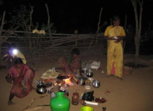 Family cooking outside hut using New lights